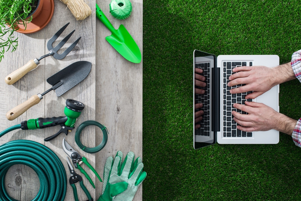 landscaping technology, Gardening tools on a table and gardener networking with a laptop, landscaping and technology concept.