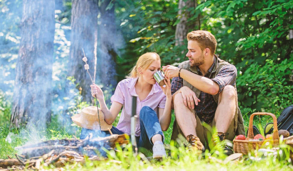 Food for hike and camping. Couple sit near bonfire eat snacks and drink