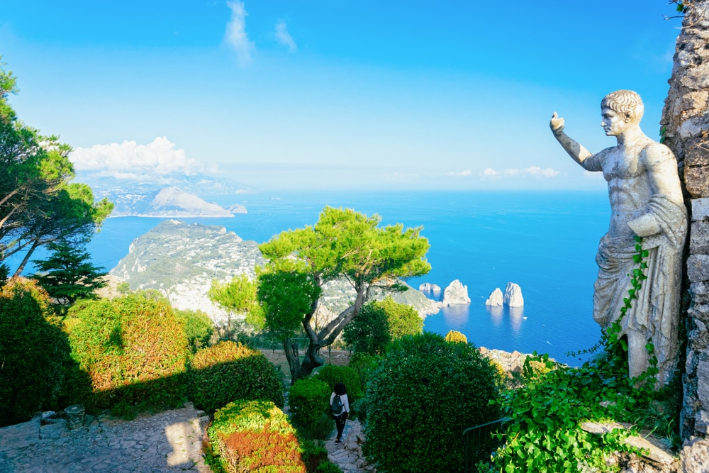Statue and gardens at Capri Island town, Italy. Landscape with sculpture and Blue Mediterranean Sea, Italian coast